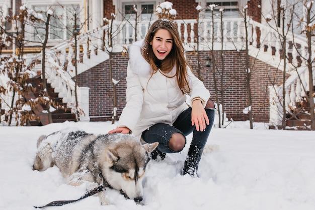 Glückliche lachende frau mit glattem haar, das auf schnee neben ihrem hund sitzt. gut aussehende frau in jeans und weißer jacke, die mit husky nach dem spaziergang im wintermorgen aufwirft.