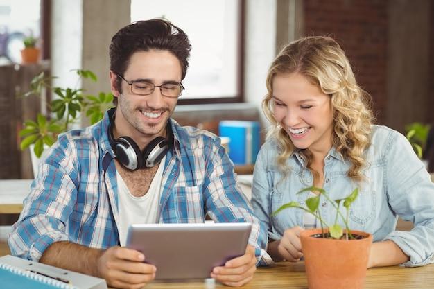 Glückliche lachende geschäftsleute beim betrachten der digitalen tablette im büro
