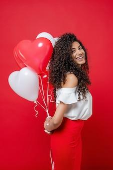 Glückliche lächelnde afrikanische frau, die zurück bunte ballone des heliums hinter ihr hält
