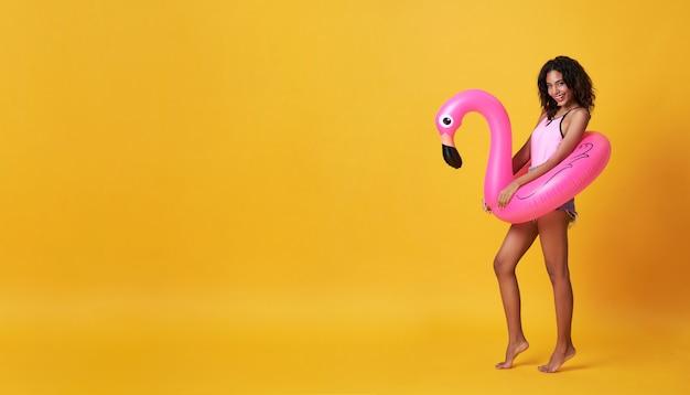 Glückliche lächelnde afrikanische frau gekleidet in badebekleidung, die flamingogummiring hält und ihren sommerferienurlaub in gelb mit kopienraum genießt.