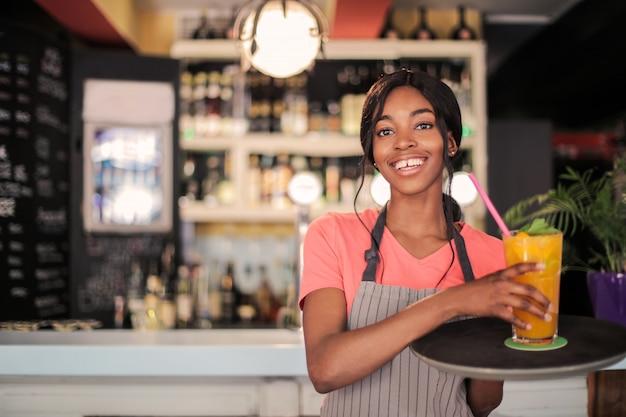Glückliche lächelnde afrokellnerin