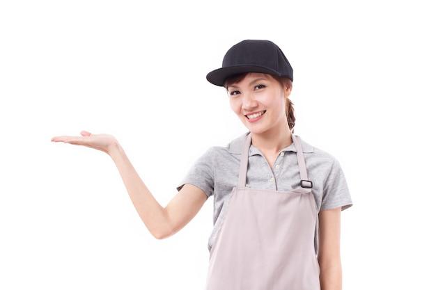 Glückliche, lächelnde arbeiterin, die präsentiert, auf leerzeichen zeigend