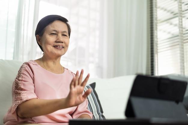 Glückliche lächelnde asiatische ältere frau, die im sofa sitzt und videoanruf auf digitalem tablett während der quarantäne und isoliert zu hause macht.