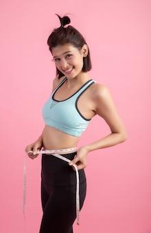 Glückliche lächelnde asiatische frau des sexy körpers des diäteignungs-übungssports mit messendem band
