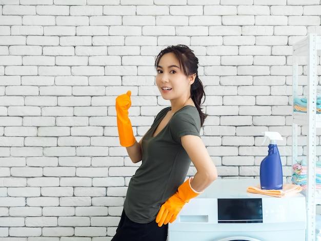 Glückliche lächelnde asiatische frau, hausfrau, die orange gummihandschuhe steht und hand in gewinnender geste anhebt und erfolg nahe waschmaschine auf backsteinmauer feiert