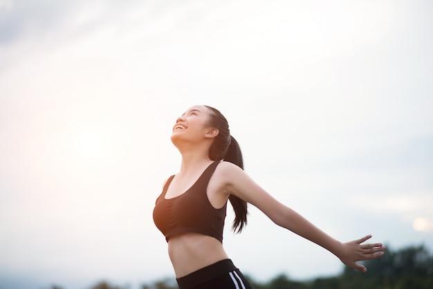 Glückliche lächelnde athletische frau mit den armen ausgestreckt