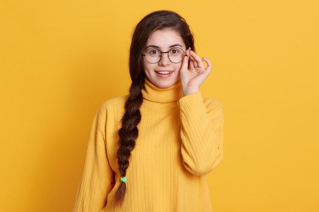 Glückliche lächelnde aufgeregte junge frau mit zopf, der gelbes hemd trägt