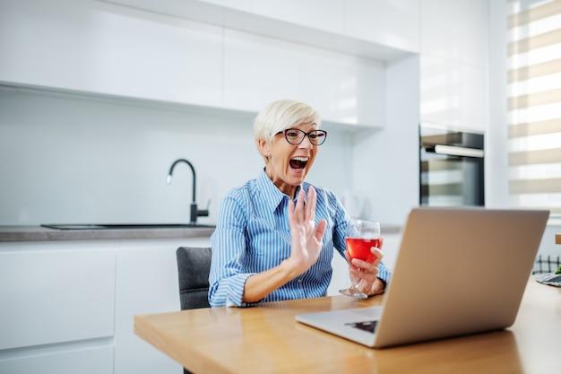 Glückliche lächelnde blonde ältere frau, die am esstisch sitzt, rotwein trinkt, videoanruf am laptop hat und winkt
