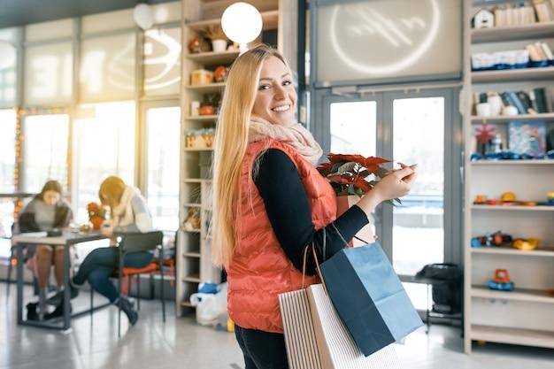 Glückliche lächelnde blondine in der kaffeestube mit einkaufstaschen und roter poinsettiaweihnachtsblume.