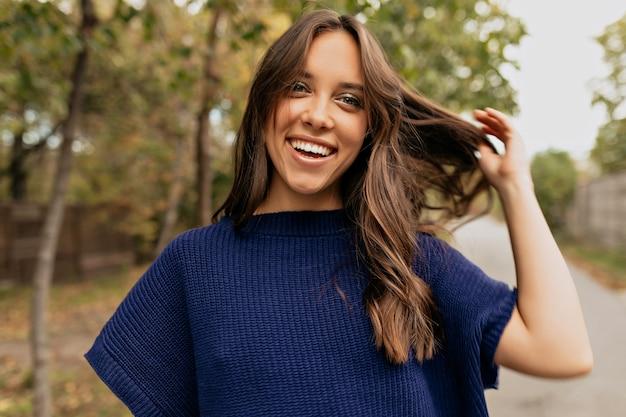 Glückliche lächelnde dame mit welligem haar, das blauen pullover trägt, der ihr haar im park berührend aufwirft