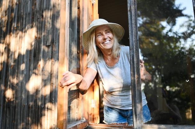 Glückliche lächelnde emotionale ältere frau, die durch offenes fenster im alten hölzernen dorfhaus im strohhut aufwirft