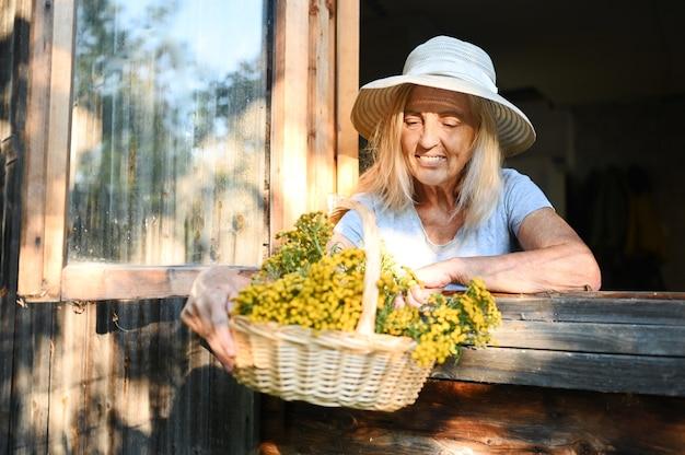 Glückliche lächelnde emotionale ältere frau, die durch offenes fenster im alten hölzernen dorfhaus im strohhut mit blumenkorb aufwirft