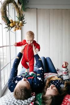 Glückliche lächelnde familie am studio auf hintergrund des weihnachtsbaums mit geschenk