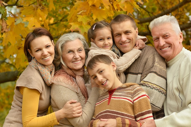 Glückliche lächelnde familie, die im herbstpark sich entspannt