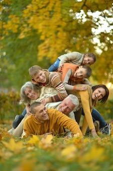 Glückliche lächelnde familie, die im herbstwald sich entspannt