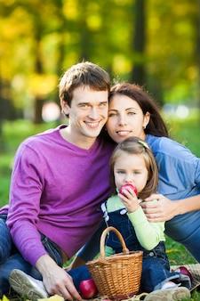 Glückliche lächelnde familie, die picknick im herbstpark hat