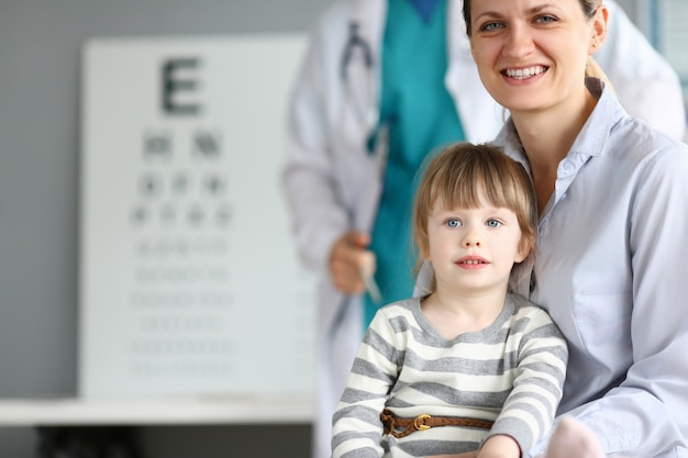 Glückliche lächelnde familie in der kinderarztpraxis