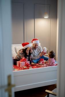 Glückliche lächelnde familie mit weihnachtsmützen, die auf dem bett mit geschenken sitzen und mit babyfrau für weihnachtsferien spielen.