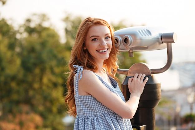 Glückliche lächelnde frau, die am teleskop steht