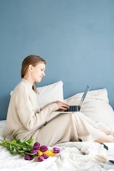 Glückliche lächelnde frau, die auf dem bett sitzt und pyjamas trägt, mit vergnügen blumen genießt und mit laptop plaudert