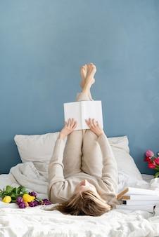 Glückliche lächelnde frau, die auf dem bett sitzt und pyjamas trägt, mit vergnügen, blumen zu genießen und ein buch zu lesen