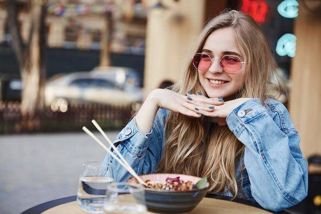 Glückliche lächelnde frau, die draußen im asiatischen restaurant isst und asid schaut