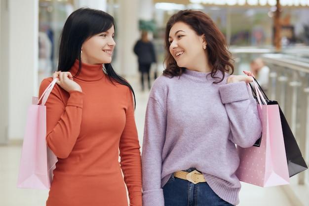Glückliche lächelnde frau, die einander beim einkaufen im einkaufszentrum betrachtet und mit taschen aufwirft