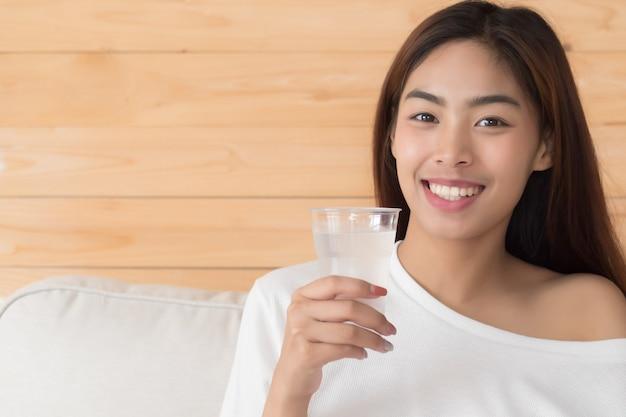 Glückliche, lächelnde frau, die frisches wasser trinkt