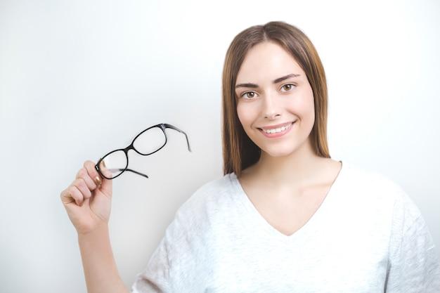 Glückliche lächelnde frau, die gläser auf weißem hintergrund hält. optik fürs sehen.