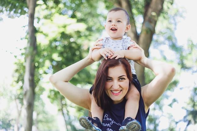 Glückliche lächelnde frau, die ihr baby auf ihren schultern im park hält