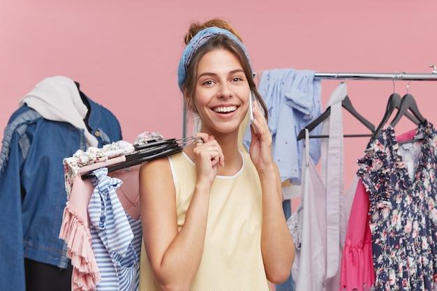 Glückliche lächelnde frau, die in der boutique mit kleidern steht, ihre freundin anruft, ihr über erfolgreichen einkaufstag und was sie kaufte, erzählt. fröhliche frau, die sich ihrer einkäufe mit dem handy rühmt