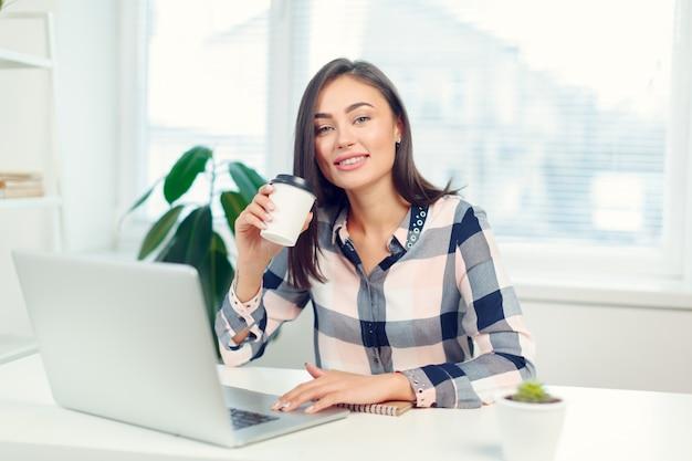 Glückliche lächelnde frau, die mit laptop arbeitet und kaffee trinkt