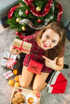 Glückliche lächelnde frau, die nahe verziertem weihnachtsbaum sitzt und ihre geschenke genießt
