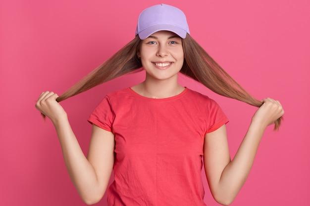 Glückliche lächelnde frau, die rotes t-shirt und baseballmütze trägt, die ihr haar beiseite schieben
