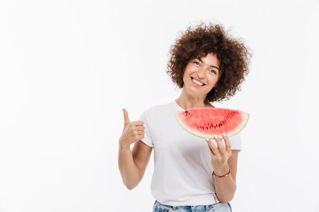 Glückliche lächelnde frau, die scheibe einer wassermelone hält