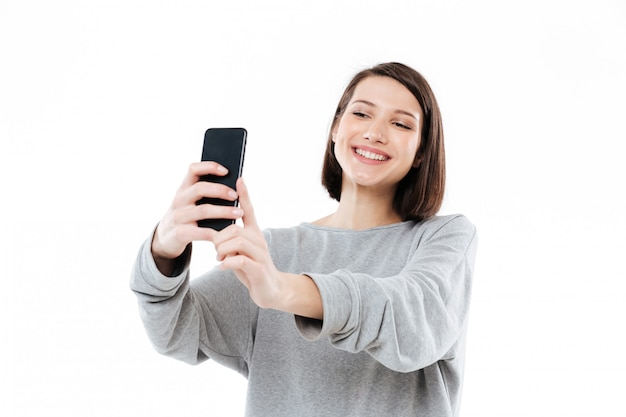 Glückliche lächelnde frau, die selfie auf handy nimmt