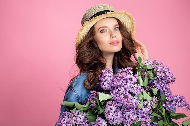 Glückliche lächelnde frau im strohhut, der mit blumenstrauß der lila blumen aufwirft