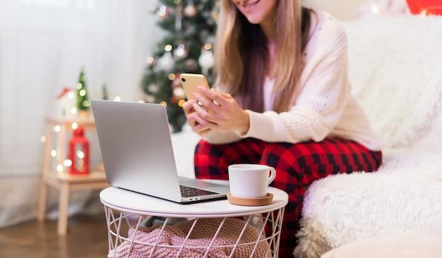 Glückliche lächelnde frau in der roten weihnachtsmütze, die einen videoanruf hat oder selfie nimmt