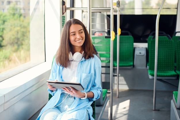 Glückliche lächelnde frau liest eine tafel oder ein e-book in einer modernen straßenbahn oder u-bahn. hübsches mädchen reitet für die arbeit im öffentlichen verkehr.