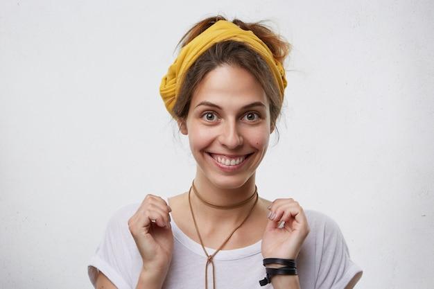 Glückliche lächelnde frau mit braunen augen, die beiläufig im weißen t-shirt und im gelben stirnband gekleidet sind. freudige attraktive hausfrau, die sich freut, ihre verwandten zu sehen. menschen, emotionen