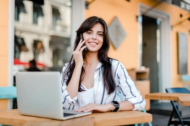 Glückliche lächelnde frau mit dem laptop, der draußen im café sitzt