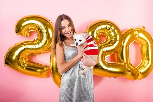 Glückliche lächelnde frau mit dem weißen hund der chihuahua und 2020 weihnachtsballonen lokalisiert über rosa