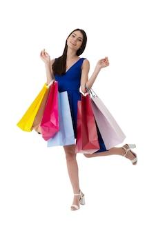 Glückliche lächelnde frau mit einkaufstüten in der hand. auf weißem hintergrund isoliert