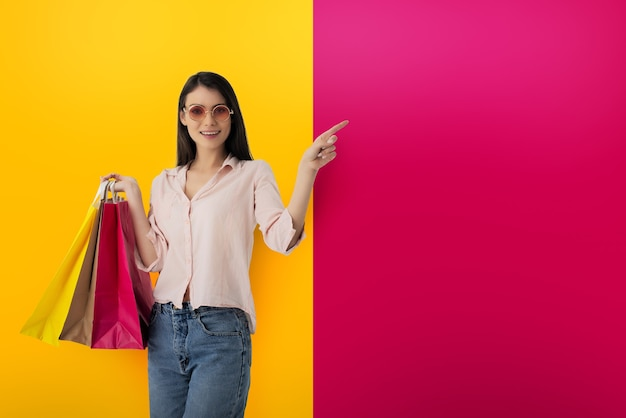 Glückliche lächelnde frau mit einkaufstüten in der hand zeigt etwas an
