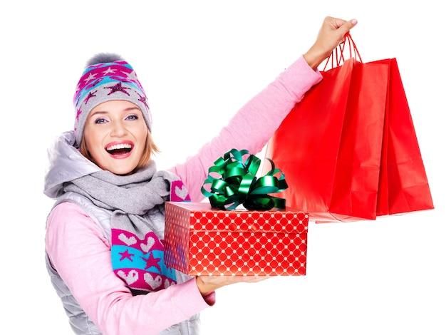 Glückliche lächelnde frau mit geschenken nach dem einkaufen lokalisiert auf weiß