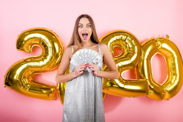 Glückliche lächelnde frau mit hundert dollarscheinen mit 2020 weihnachtsballonen getrennt über rosa