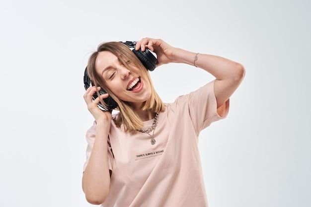 Glückliche lächelnde frau mit kopfhörern, die musik hören und tanzen