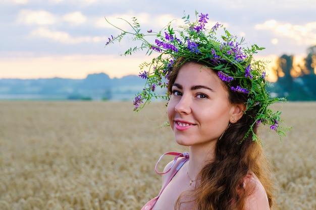 Glückliche lächelnde frau mit langen haaren mit einem blumenkranz auf kopf