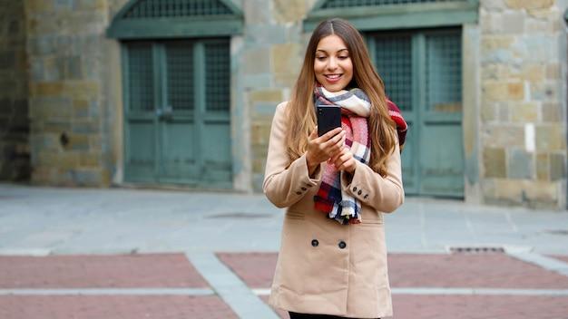 Glückliche lächelnde frau mit mantel und schal unter verwendung des smartphones im freien in der stadtstraße. speicherplatz kopieren.