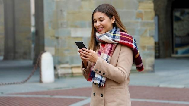 Glückliche lächelnde frau mit mantel und schal unter verwendung des smartphones im freien in der stadtstraße